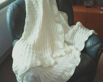 Cream Aran knitted throw.