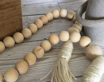 Wooden natural casa bead garland with string tassels.