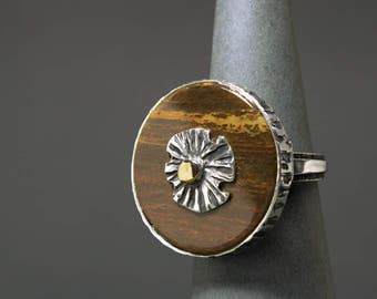 Handmade silver ring with a petrified wood and gold element