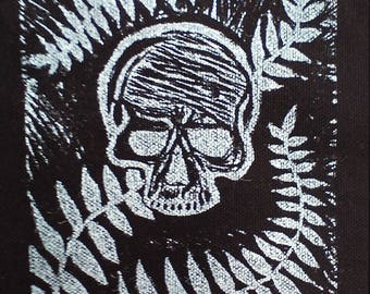 Skull and fern patch in white on black