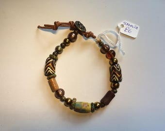 Earthy coloured Boho-chic bracelet handmade with trade beads. For festivals and summer wear. Fastens with oval shell button.