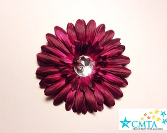 One burgundy hair flower with a rhinestone. Portion of sale goes to charity.