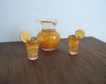 Miniature jug of orange juice with two glasses