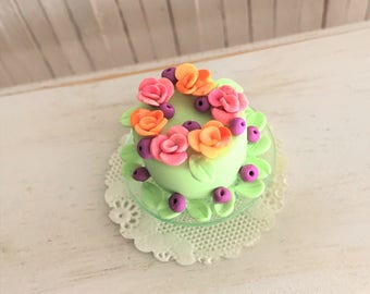 Miniature Couture Cake With Pink And Orange Roses, Blueberries, Leaves, On A Green Glass Cake Stand