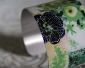 A wide, metal /aluminium cuff bracelet - made from a design of vintage ceramic images collaged and pressed into the metal cuff