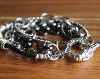 Black leather, silver tone, and gunmetal gray chain bracelet with toggle clasp