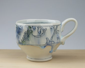 Handmade porcelain mug with toile pattern and ornate handle
