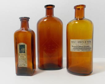 3 amber or brown bottles  great for displaying or collecting All have cork finishes