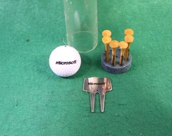 Vintage scarce rare Microsoft golf ball, divot tool and (6) tee set.