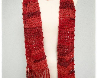 Crochet fringed scarf in red shades.