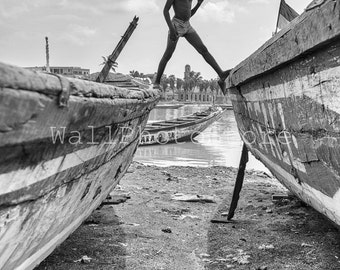 Travel Photography, Boy walking on the Boats in St.Luis, Senegal, Black and White Photography, Fine Art Photography, Vertical Wall Art Print