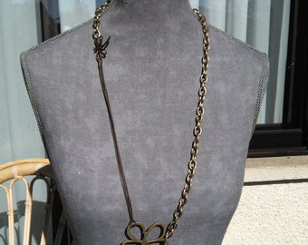 Long necklace with flower and dragonfly in light gold tone. Necklace with metal chain.