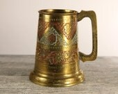 Engraved brass drinking tankard with glass bottom