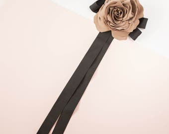Light brown flower brooch with a black bow made from ribbon, bow tie brooch with flower