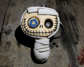 Happy baby mummy keychain in dirty white. Creepy and cute skull with a blue and orange flower in his eye.