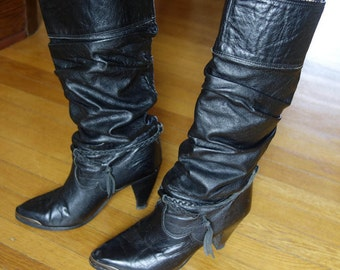 Black leather Zodiac vintage 1980's boots knee high or slouch glam rock disco braided tassels metal toe guards shaped high western heel 7 M