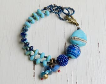All the blues - handmade artisan bead bracelet with lampwork and handwoven glass, in aqua cobalt and navy blues - Songbead, UK, narrative