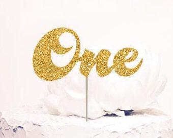 One Cake Topper, First birthday. Chic birthday decor. Gold Glitter. Cursive Script letters.