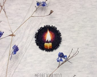 A small round hand embroidered brooch with candles. Embroidered jewelry