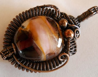 Round pink swirled bead pendant wrapped and woven with oxidized copper wire