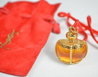 Yves Saint laurent dije colgante con cinta roja y estuche ámbar y dorado