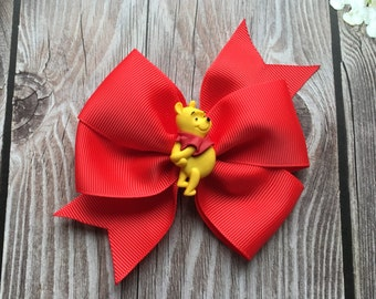 Winnie the Pooh pinwheel hair bow on red ribbon with Pooh in the center on an alligator clip