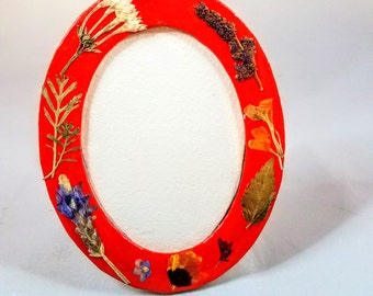 Small oval Picture Frame, sturdy cardboard, three coats of cheery red acrylic paint, pressed flower strewn, archival Varnish,  Easel back,