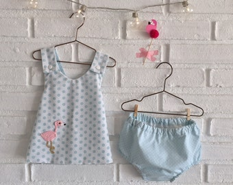 Dress and blue polka dots cubrepanal with crochet and cross baby back wall.