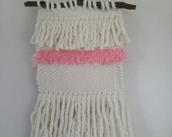 Hand woven wall hanging in cream and pink