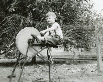 This Little Boy Has an AX TO GRIND As He Sits On Top of a Grinding Wheel Photo 1953