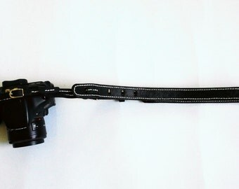 White stitched on black leather camera strap,