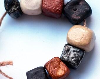The idea of deserving -- a set of 8 cubic metallic, dark, iridescent ceramic  beads