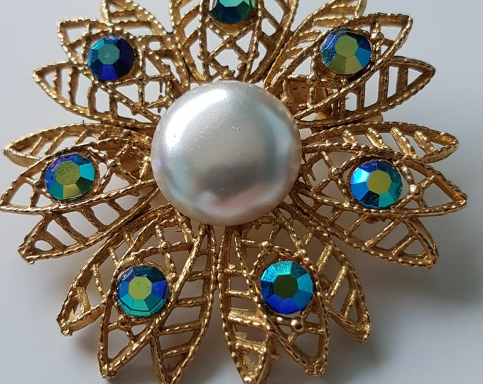 Vintage gold tone filigree flower shaped brooch with faux pearl and turquoise shimmer rhinestones.