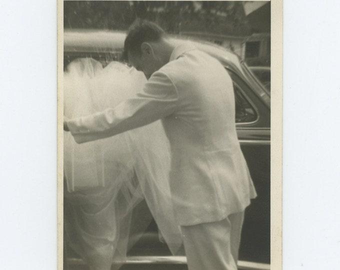 Groom Helps Bride Into Car in Shower of Rice, c1950s: Vintage Snapshot Photo (71539)