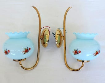 A pair of brass sconces with pale blue glass shades and floral motifs