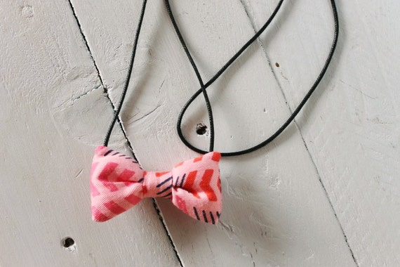 Bow necklace >> Pink, red, blue patterned arrow bow on black cord >> Brisbane