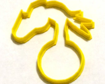 Some one hand holding a xmax ball cookie cutter