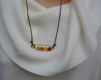 Safety pin necklace is hand made with a brass safety pin and Blue Moon beads