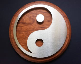 Brushed stainless steel disk with laser-cut Yin Yang design floating on wood disk (Jatoba)
