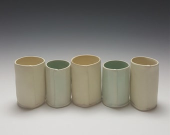 Handmade set of ceramic shot glasses by Potteryi.  Modern set in blue celadon and satiny cream.