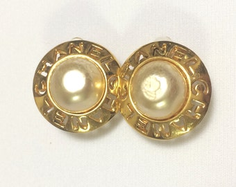 Vintage CHANEL golden round shape faux pearl earrings with cutout logo. Chic and elegant look.