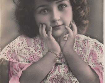 Soulful eyes, sweet girl, vintage child, charm bracelet, pink dress, white lace, hand tinted, gold detail, 1900s girl photo  (rppc/ch369)