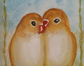 Pair of love birds on a swing