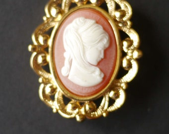 Vintage faux cameo brooch, girl with ponytail on orange background, gold tone surround