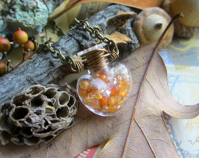 Vial necklace filled with amber color faceted Agate and Swarovski crystals. Custom length chain.
