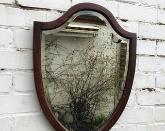 Antique oak shield mirror with patina and bevelled glass
