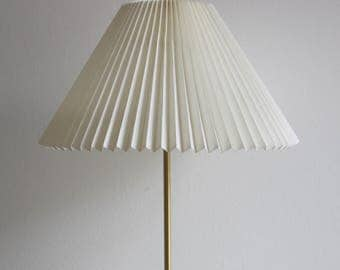 A brass lamp with a white hand-pleated shade designed by Esben Klint in 1948 for Le Klint