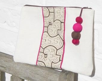 Pompom and shipibo fabric clutch bag