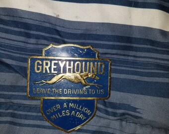 Advertising greyhound hat badge leave the driving to us over a million miles a day