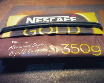 Zero waste credit card wallet made from upcycled Nescafé gold packaging.